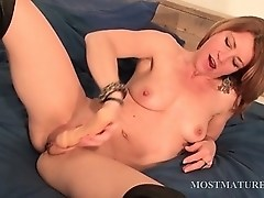Mature hottie dildoes her cunt in bed